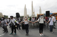 Anti-government protesters hold the hands together for security during a protest near Democracy Monument in Bangkok, Thailand, Wednesday, Oct. 14, 2020. Thai political activists hope to keep up the momentum for their campaign for democratic change with their third major rally in the capital Bangkok on Wednesday. (AP Photo/Sakchai Lalit)