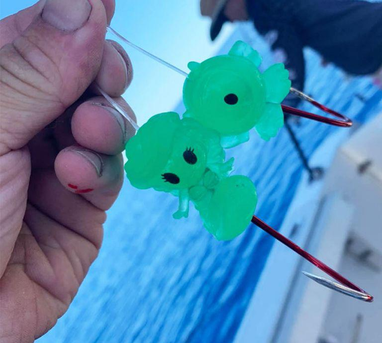 Person holding fishing hooks with two glow in the dark Ooshies.