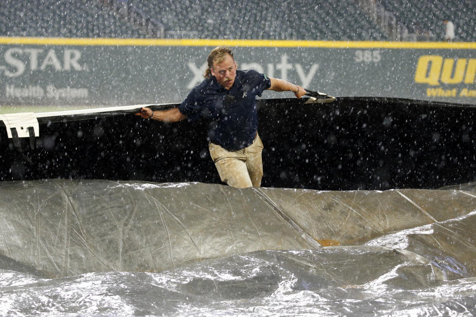 A member of the Atlanta Braves grounds crew works to cover the field during a rain shower in the seventh inning of a baseball game between Cincinnati Reds and the Braves on TThursday, Aug. 1, 2019, in Atlanta. (AP Photo/John Bazemore)
