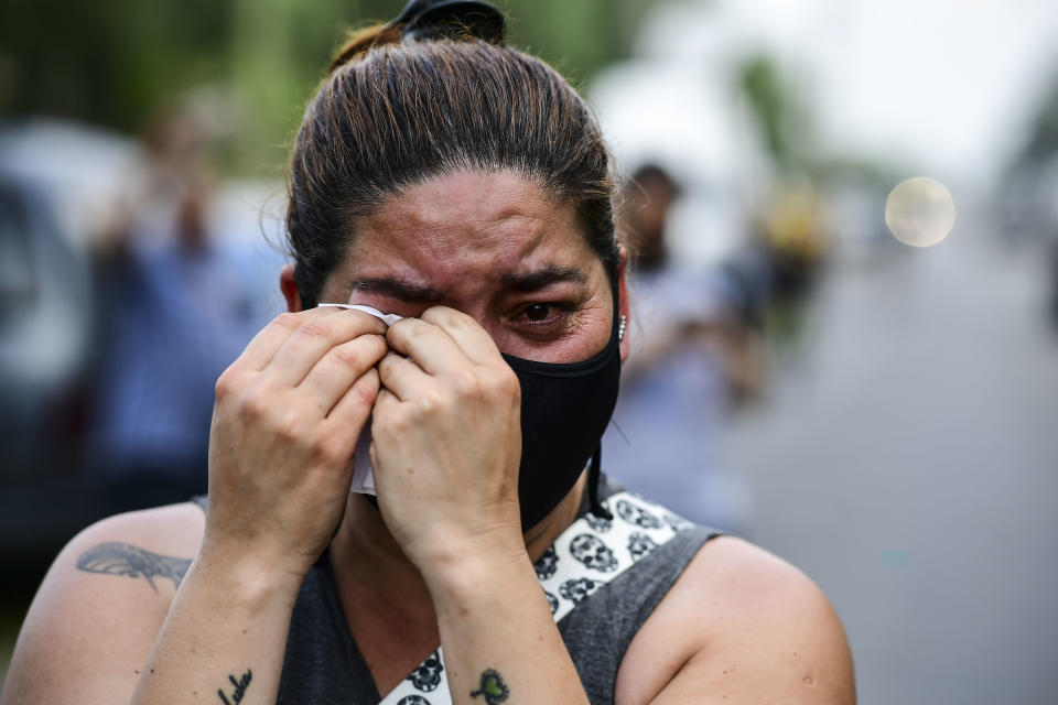 A woman mourns outside the gated community where Argentine football star Diego Maradona's home is located, in Benavidez, Buenos Aires province, where he died on November 25, 2020. (Photo by RONALDO SCHEMIDT / AFP) (Photo by RONALDO SCHEMIDT/AFP via Getty Images)