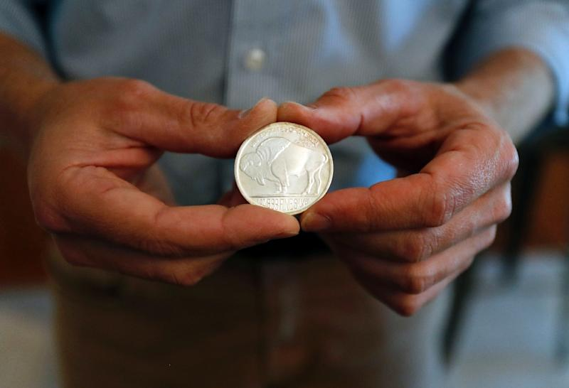 'Prepper' Adam Taggart holds a silver ounce coin which equals about $18.20 in today's market value (AFP Photo/MONICA DAVEY)