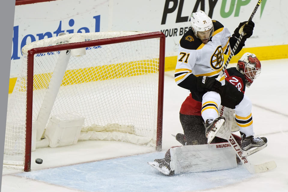 The puck goes in on a shot by Boston Bruins left wing Taylor Hall (71) who leaps above New Jersey Devils goaltender Mackenzie Blackwood (29) during the second period of an NHL hockey game, Tuesday, May 4, 2021, in Newark, N.J. The goal was ruled good after a video review. (AP Photo/Kathy Willens)