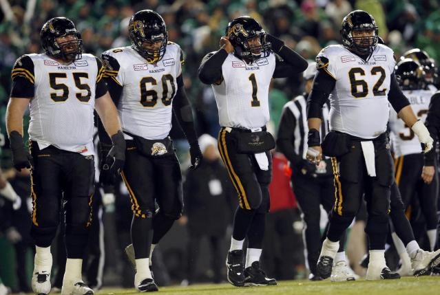 Hamilton Tiger-Cats quarterback Henry Burris (1) walks off the field with teammates Tim O'Neill (55), Joel Figueroa (60) and Marwan Hage (62) during the second half of the CFL's 101st Grey Cup championship football game against teh Saskatchewan Roughriders in Regina, Saskatchewan November 24, 2013. REUTERS/Mark Blinch (CANADA - Tags: SPORT FOOTBALL)