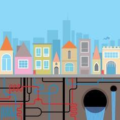 A drawing of houses in a city with water pipes and sewers underground