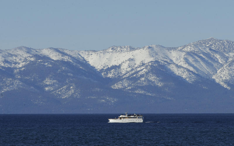 FILE - In this March 5, 2018 file photo snow covers the mountain tops as a boat crosses Lake Tahoe, in South Lake Tahoe, Calif. Scientists at Lake Tahoe say the clarity of the alpine lake that straddles the California-Nevada line sank to an all-time low last year. Experts say the 9.5-foot (2.8-meter) decline was most likely due to a convergence of drought, record precipitation and warm temperatures. (AP Photo/Rich Pedroncelli,File)