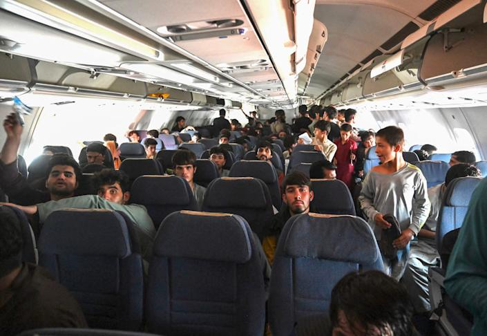 Afghan passengers sit inside a plane as they wait to leave the Kabul airport in Kabul on August 16, 2021. (Wakil Kohsar /AFP via Getty Images)