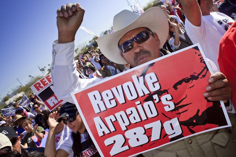 A man holds up sign calling for the Department of Homeland Security to revoke the Maricopa County Sheriff's authority under the 287(g) program to investigate immigration crimes, in Phoenix, Ariz., Feb. 28, 2009