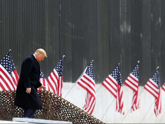 President Donald Trump walks down the steps before a speech near a section of the US Mexico border wall (AP)