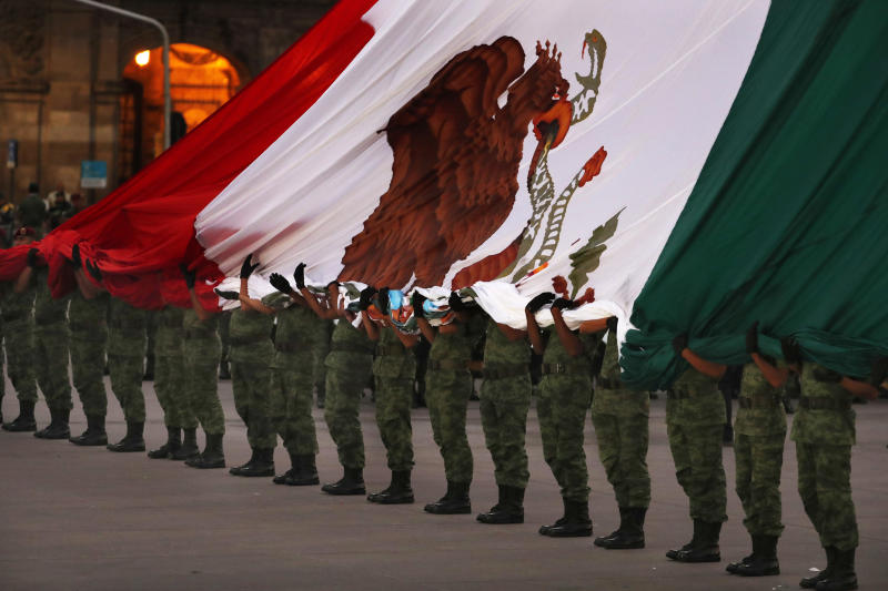 Soldiers hold a Mexican national flag as it is raised at half-staff during the 34th anniversary of the 1985 earthquake, in Mexico City, Thursday, Sept. 19, 2019. The 8.1-magnitude earthquake killed as many as 10,000 and left thousands homeless. The date also commemorates the 2017 earthquake that rattled the city killing hundreds. (AP Photo/Marco Ugarte)