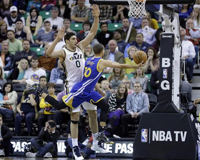 Golden State Warriors' Stephen Curry (30) lays the ball up as Utah Jazz's Enes Kanter (0) defends in the fourth quarter of an NBA basketball game Friday, Jan. 31, 2014, in Salt Lake City. Warriors won 95-90. (AP Photo/Rick Bowmer)