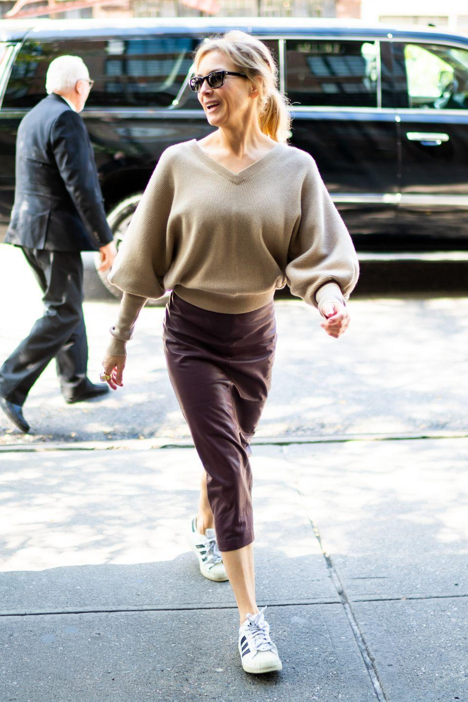 """<p>A cozy sweater paired with a streamlined leather pencil skirt is an evergreen combination. But do as <a href=""""https://www.townandcountrymag.com/leisure/arts-and-culture/a29026941/renee-zellweger-judy-garland-interview/"""" rel=""""nofollow noopener"""" target=""""_blank"""" data-ylk=""""slk:Renee Zellweger"""" class=""""link rapid-noclick-resp"""">Renee Zellweger</a> did and throw in a surprise—sporty accessories like Adidas sneakers and a smart watch—to give the look an unexpected air of casual nonchalance.</p>"""