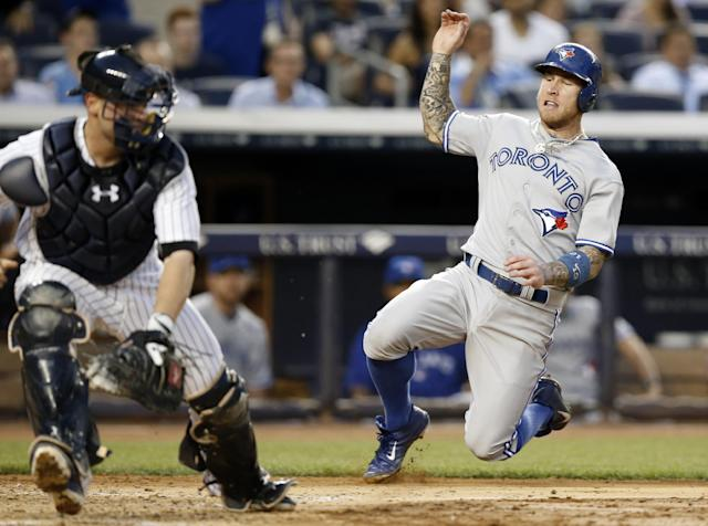 New York Yankees catcher Brian McCann, left, reaches for a wide throw as Toronto Blue Jays Brett Lawrie, right, scores on Colby Rasmus's fourth-inning RBI single in a baseball game at Yankee Stadium in New York, Wednesday, June 18, 2014. (AP Photo/Kathy Willens)
