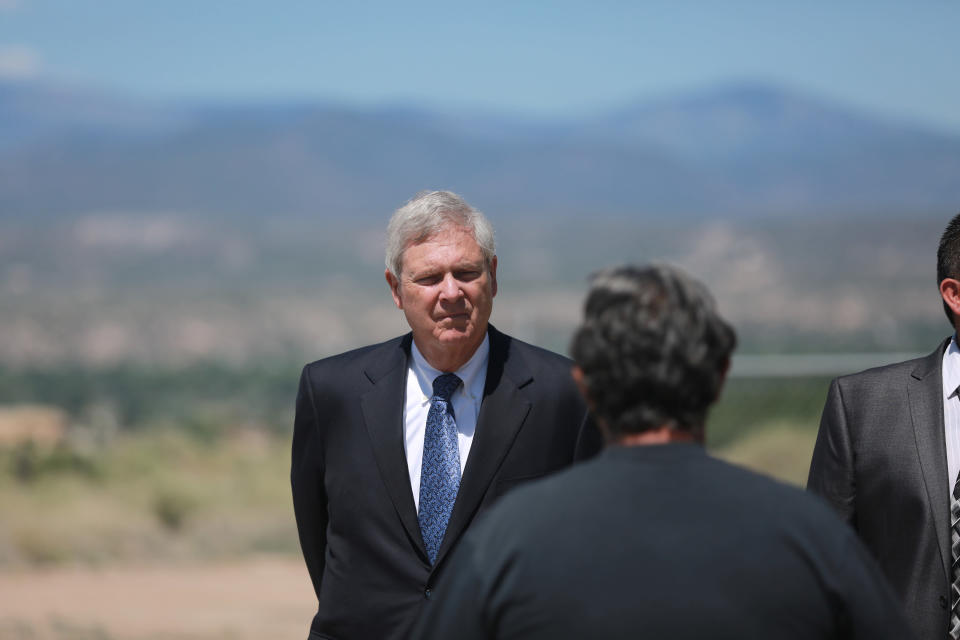 Agriculture Secretary Tom Vilsack speaks with wastewater manager Nelson Edmonds on Wednesday, July 7, 2021, in Ohkay Owingeh, N.M. Vilsack announced that the Pueblo will receive a $610,000 loan and a $1.6 million grant in state money to expand the wastewater treatment plant where Edmonds works. (AP Photo/Cedar Attanasio)