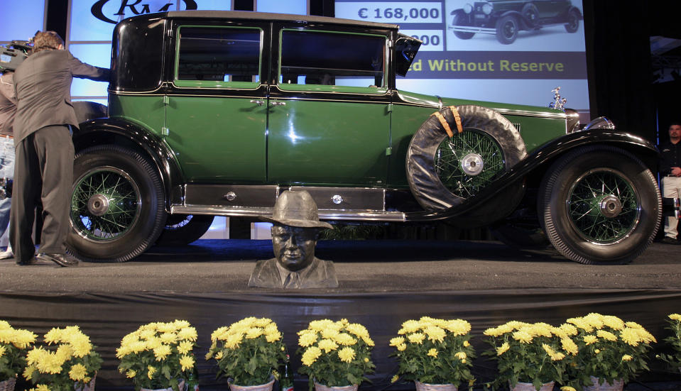 This 1928 Cadillac V8 Town Sedan, originally bulletproof, was once owned by Al Capone and sold for 621,500 dollars at the RM Vintage Motor Cars in Arizona auction at the Arizona Biltmore Resort in Phoenix, Arizona January 20, 2006. The car had been the property of the Smokey Mountain Car Museum in Tennessee. At the bottom is a bust of Al Capone. REUTERS/Jeff Topping