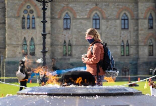 A person in sunglasses and a mask walks past the Centennial Flame in Ottawa on Sept. 30, 2021, during the COVID-19 pandemic. On Sunday, health officials in the city reported 64 new cases of the illness. (Trevor Pritchard/CBC - image credit)