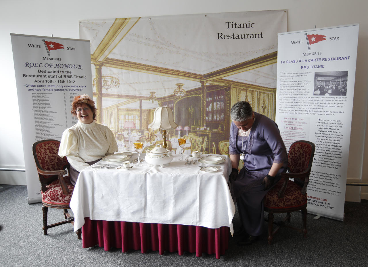 Sisters Terri Williamson, left and Tracie Brelsford from Washington state in the US pose for their photograph as they sit in a mock up of a first class dinning table from the Titanic in the check in area for the MS Balmoral's Titanic memorial cruise in Southampton, England, Sunday, April 8, 2012. Nearly 100 years after the Titanic went down, a cruise with the same number of passengers aboard is setting sail to retrace the ship's voyage, including a visit to the location where it sank. The Titanic Memorial Cruise is set to depart Sunday from Southampton, where the Titanic left on its maiden voyage. The 12-night cruise will commemorate the 100th anniversary of the sinking of the White Star liner. With 1,309 passengers aboard, the MS Balmoral will follow the same route as the Titanic. Organizers are trying to recreate the onboard experience minus the disaster from the food to a band playing music from that era. Organizers said people from 28 countries have booked passage, including relatives of some of the more than 1,500 people who died when the Titanic collided with an iceberg and sank on April 15, 1912.(AP Photo/Alastair Grant)