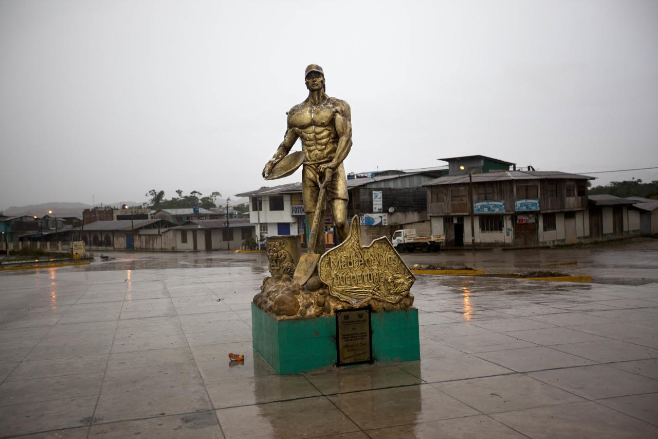 In this May 20, 2014 photo, a golden statue of a miner holding a shovel and plate stands in the empty central square of Huepetuhe in the Madre de Dios region of Peru. Thousands of people have left the Peruvian Amazon boomtown since the government halted gasoline shipments in April and sent troops to destroy heavy machinery used in mining that it deemed illegal. (AP Photo/Rodrigo Abd)