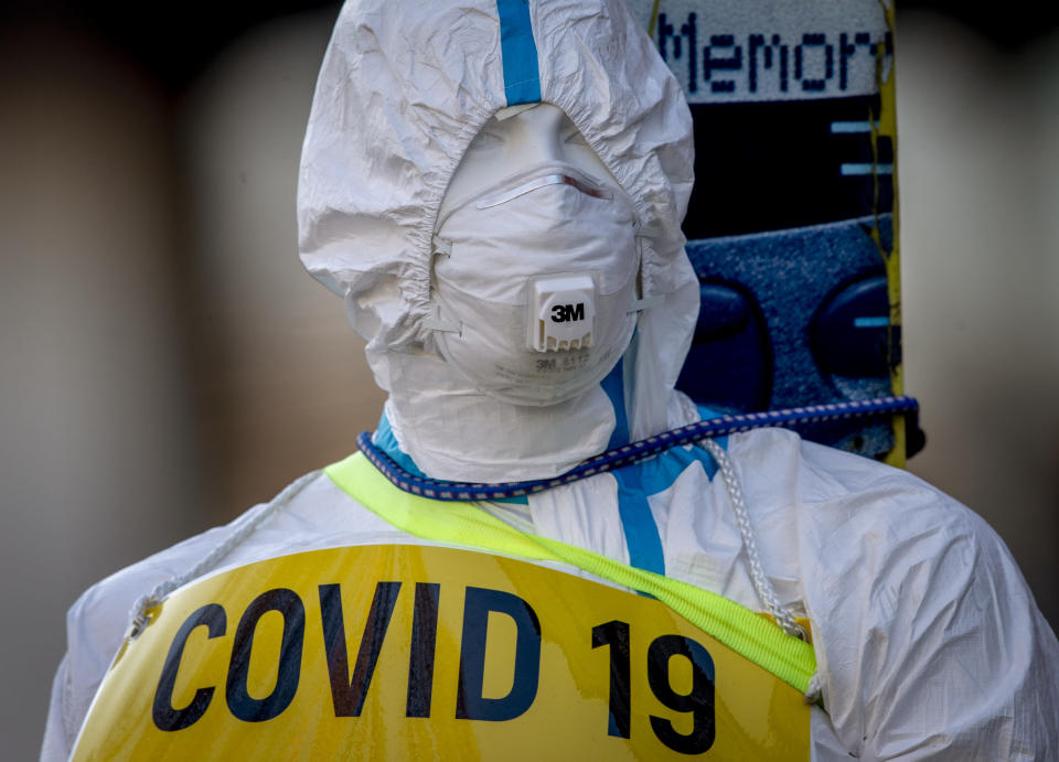 An advertising figure for Covid-19 rapid test stands in front of a small test center in Frankfurt, Germany, Sunday, March 7, 2021. From Monday on free corona tests are offered in Germany. (AP Photo/Michael Probst)