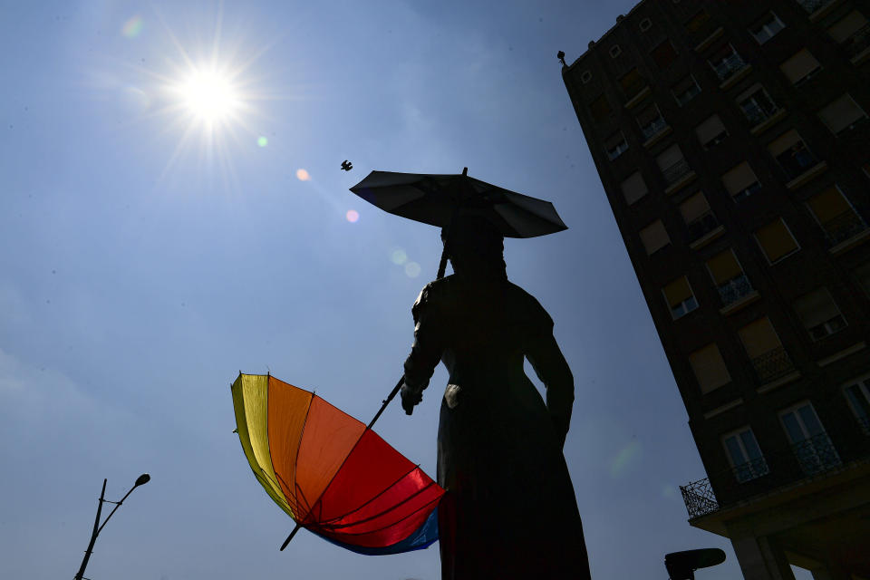 A rainbow colored umbrella is attached to a statue before a gay pride parade in Budapest, Hungary, Saturday, July 24, 2021. Hungary's government led by right-wing Prime Minister Viktor Orban passed a law in June prohibiting the display of content depicting homosexuality or gender reassignment to minors, a move that has ignited intense opposition in Hungary while EU lawmakers have urged the European Commission to take swift action against Hungary unless it changes tack. (AP Photo/Anna Szilagyi)