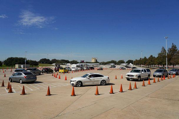 PHOTO: Voters in cars line up at a drive-through mail ballot drop-off site at NRG Stadium on Oct. 7, 2020 in Houston. (Go Nakamura/Getty Images)
