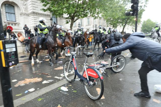 A bicycle is thrown at mounted police Police on horseback in Whitehall following a Black Lives Matter protest on Saturday. (PA)