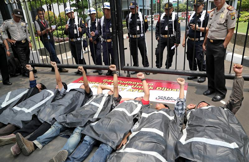 Students shout slogans while lying in front of the gate during a demonstration against the Asia-Pacific Economic Cooperation (APEC) forum being held in the Indonesian resort island of Bali, outside the Finance Ministry building in Jakarta, Indonesia, Monday, Oct. 7, 2013. Leaders of the Asia-Pacific Economic Cooperation forum, meeting amid tight security on this tropical island in eastern Indonesia, urged faster work on reforms meant to break down trade barriers and improve competitiveness. (AP Photo/Tatan Syuflana)