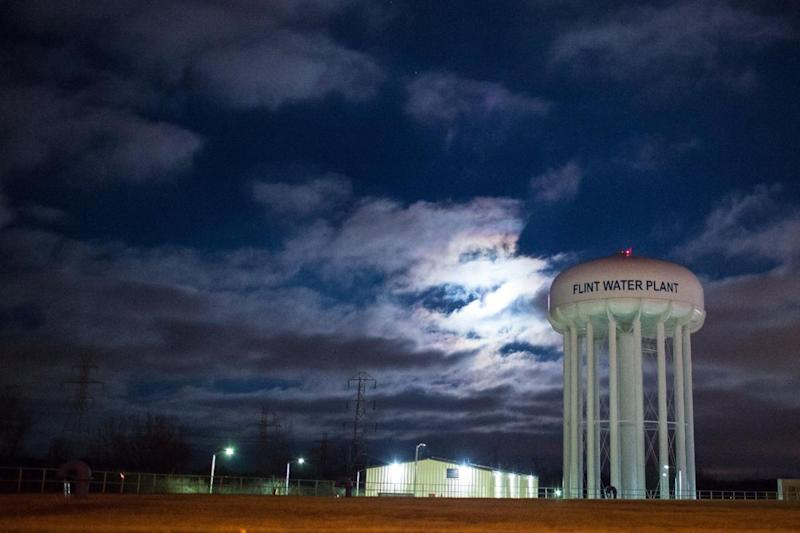 The City of Flint Water Plant is illuminated by moonlight.