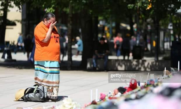 A photograph of Loretta John mourning residential school victims at a memorial in Vancouver is being licensed by Getty Images for up to $575. John, who gave CBC permission to use the image, says she wants any profits to be given to residential school survivors and support groups. (Mert Alper Dervis/Getty Images - image credit)