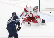 Columbus Blue Jackets forward Nick Foligno, left, scores past Carolina Hurricanes goalie James Reimer during the second period of an NHL hockey game in Columbus, Ohio, Sunday, Feb. 7, 2021. (AP Photo/Paul Vernon)