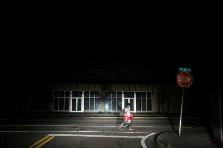 A man walks back home in the darkness as many areas of Miami still without electricity after Hurricane Irma strikes Florida, in Little Havana, Miami, Florida, September 11, 2017. REUTERS/Carlos Barria