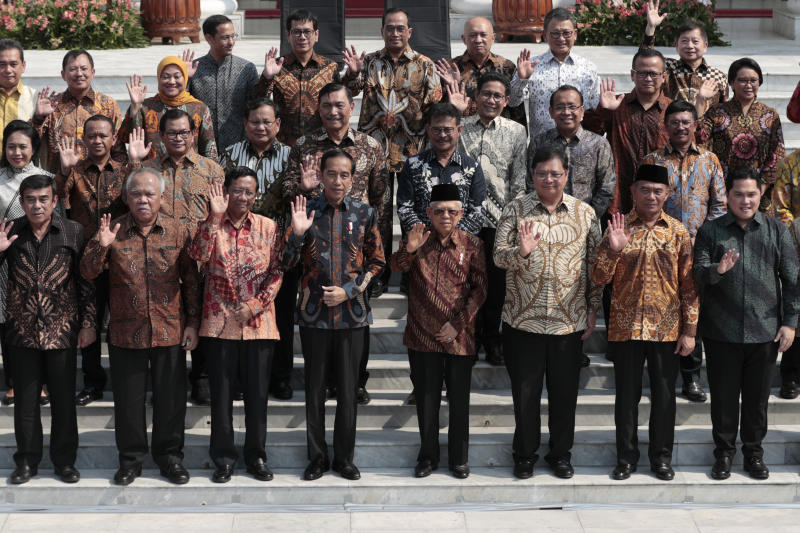 Indonesian President Joko Widodo, front row fourth from left, and his deputy Ma'ruf Amin, fifth from left, wave at the media as they pose for photographers with their new cabinet ministers during the announcement of the new cabinet at Merdeka Palace in Jakarta, Indonesia, Wednesday, Oct. 23, 2019. (AP Photo/Dita Alangkara)