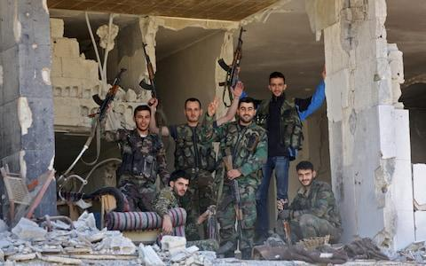 <span>Syrian soldiers wave inside a destroyed building nearly a week after retaking the town of Harasta from the rebels, in Eastern Ghouta</span> <span>Credit: AFP </span>