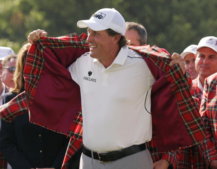 FILE - Phil Mickelson puts on the traditional red plaid jacket after winning the Colonial golf tournament in Fort Worth, Texas, in this Sunday, May 25, 2008, file photo. The Colonial begins Thursday, May 27, 2021, and is expected to be two-time Colonial champion Phil Mickelson's final tournament before his hometown U.S. Open. (AP Photo/Donna McWilliam, File)