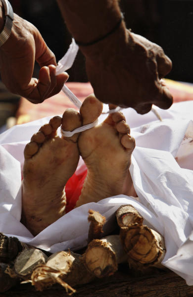 A family member performs last rites of Swapna Reddy, only feet seen, killed in Thursday's explosion, at a crematorium in Hyderabad, India, Friday, Feb. 22, 2013. Indian police are investigating whether a shadowy Islamic militant group was responsible for a dual bomb attack that killed 16 people outside a movie theater and a bus station in the southern city of Hyderabad, a police official said Friday. (AP Photo/Mahesh Kumar A.)