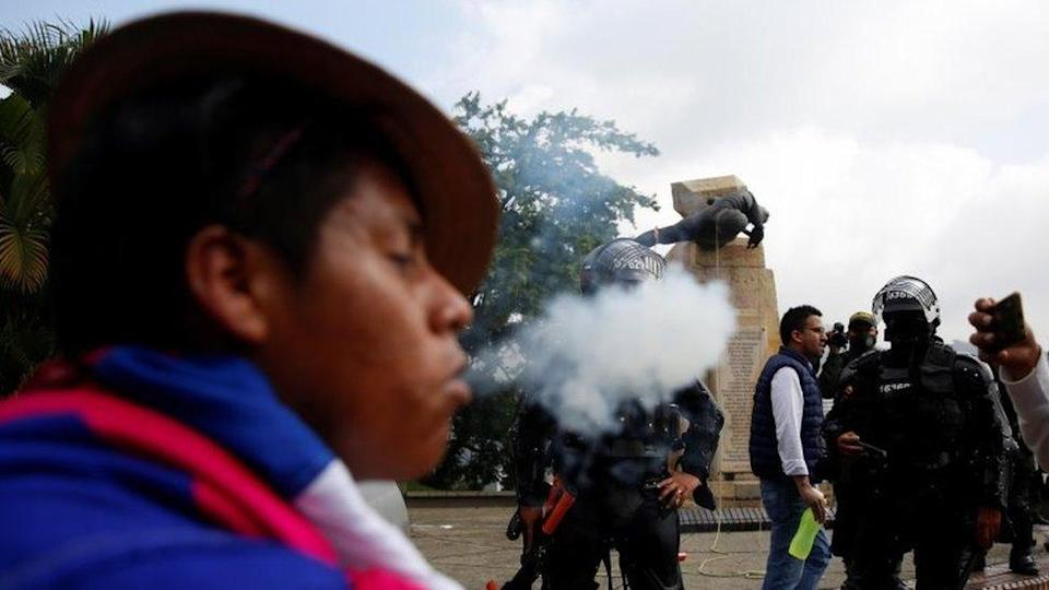 """An indigenous person performs a ritual in front of the authorities after protesters knocked down the statue of the founder of the city, Spanish conqueror Sebastian de Belalcazar, during the protests against the tax reform called by the workers"""" centrals in Cali, Colombia, 28 April 2021."""