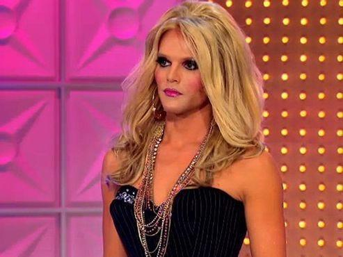Willam in a black dress and blonde wing on drag race stage