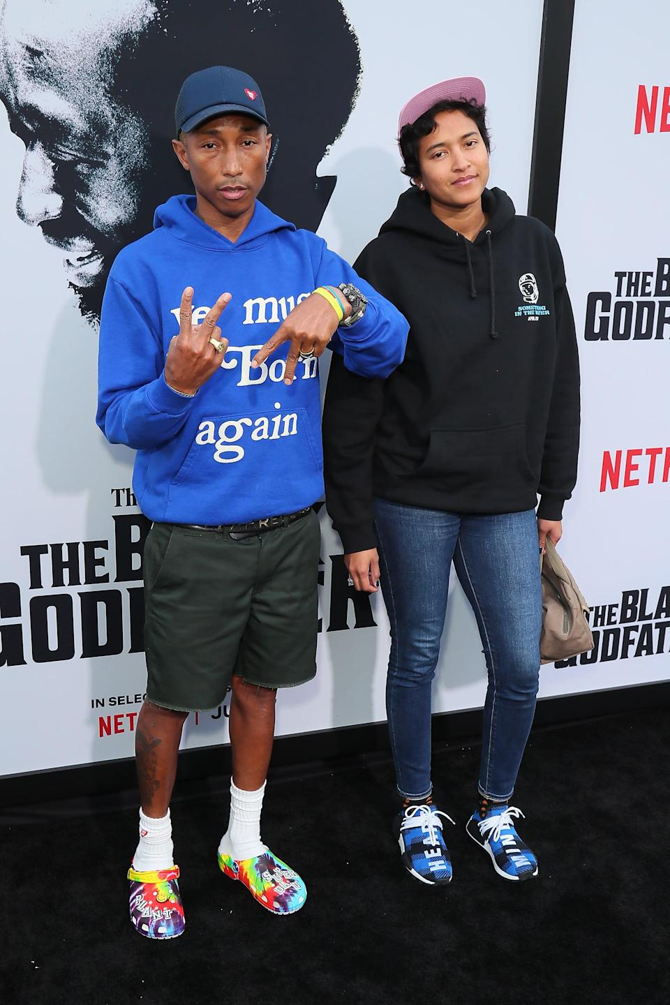 <p>Pharrell wearing tie-dye Crocs on the red carpet with shorts and a hoodie.</p>