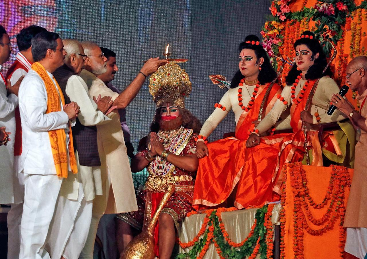 India's Prime Minister Narendra Modi (5th L) prays in front of artists dressed as Hindu gods Hanuman (C), Rama (3rd R) and Laxman during Vijaya Dashmi or Dussehra festival celebrations in Lucknow, India, October 11, 2016. REUTERS/Pawan Kumar