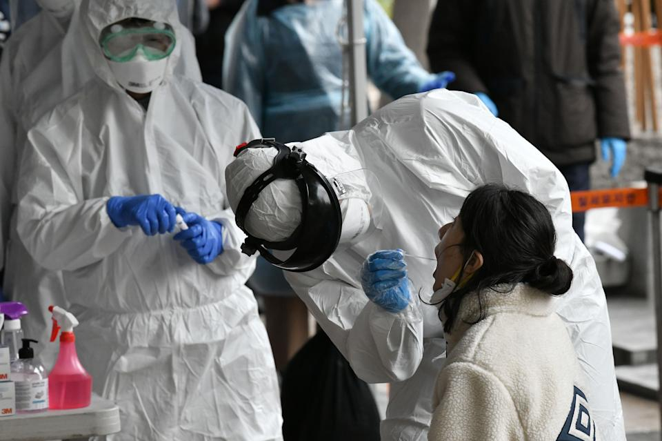 Medical staff members wearing protective gear take samples from workers at a building where 46 people were confirmed to have the COVID-19 coronavirus, at a temporary virus test facility in Seoul.