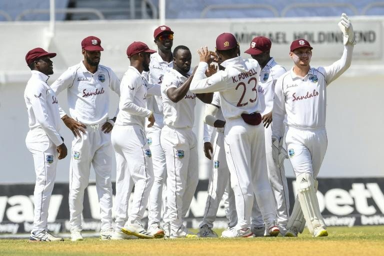 Early strikes: Kemar Roach (fourth left) and teammates celebrate the dismissal of Abid Ali