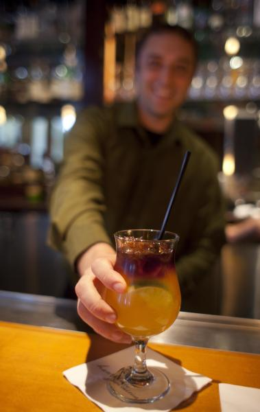 In this photo taken Monday, Aug. 6, 2012, bartender James Smith delivers a $5 Mai Tai during happy hour at the Roy's restaurant in San Francisco. The concept of happy hour when bars offer lower prices or two-for-one specials seems like a widespread tradition, but is actually illegal or restricted in quite a few places. (AP Photo/Eric Risberg)