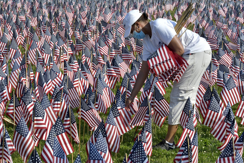 A volunteer places American flags on Boston Common ahead of Memorial Day, Wednesday. May 26, 2021, in Boston. After more than a year of isolation, American veterans are embracing plans for a more traditional Memorial Day. They say wreath-laying ceremonies, barbecues at local vets halls and other familiar events are a welcome chance to reconnect with fellow service members and renew solemn traditions honoring the nation's war dead. (AP Photo/Josh Reynolds)