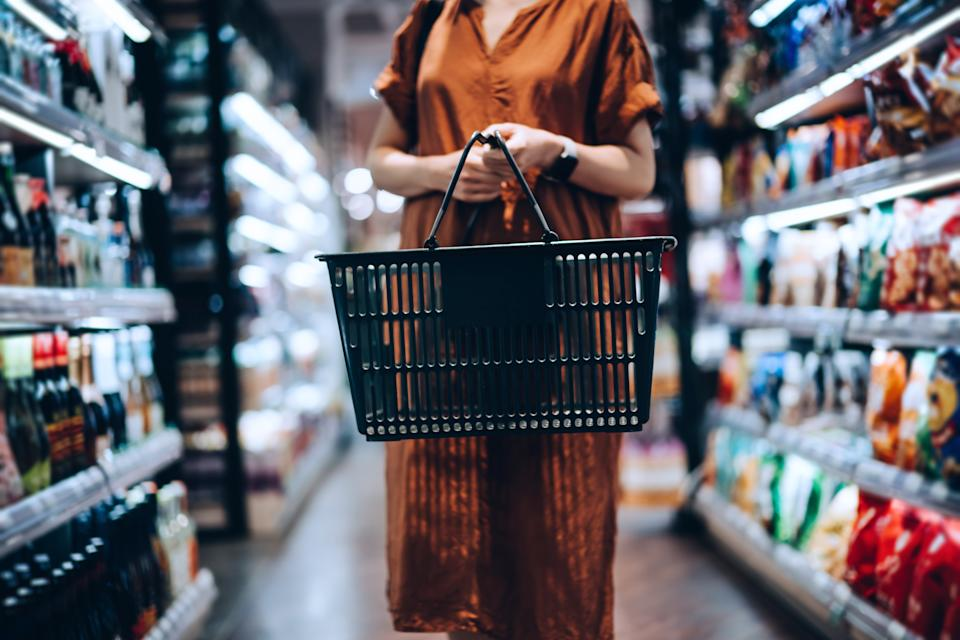 Cropped shot of young woman carrying a shopping basket, standing along the product aisle, grocery shopping for daily necessities in supermarket