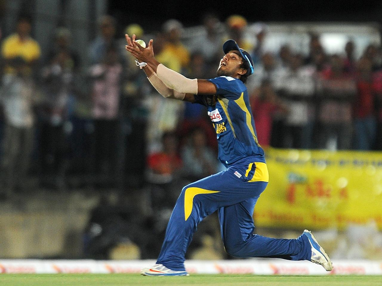 Sri Lankan cricket captain Dinesh Chandimal takes a catch to dismiss South African batsman David Miller during the second Twenty20 cricket match between Sri Lanka and South Africa at the Suriyawewa Mahinda Rajapakse International Cricket Stadium in the southern district of Hambantota on August 4,2013. AFP PHOTO / LAKRUWAN WANNIARACHCHI