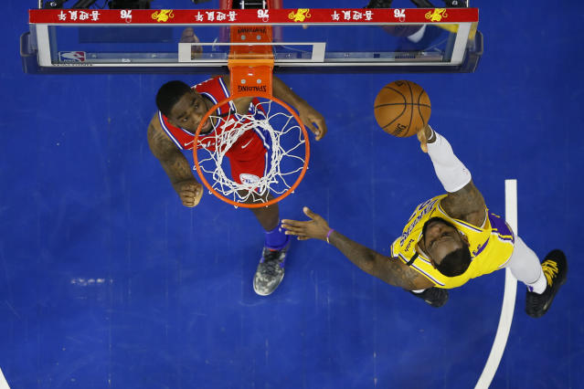 Los Angeles Lakers' LeBron James, right, puts up the ball with Philadelphia 76ers' Shake Milton, left, defending during the second half of an NBA basketball game, Saturday, Jan. 25, 2020, in Philadelphia. LeBron James passes Kobe Bryant for third on the NBA all-time scoring. (AP Photo/Chris Szagola)