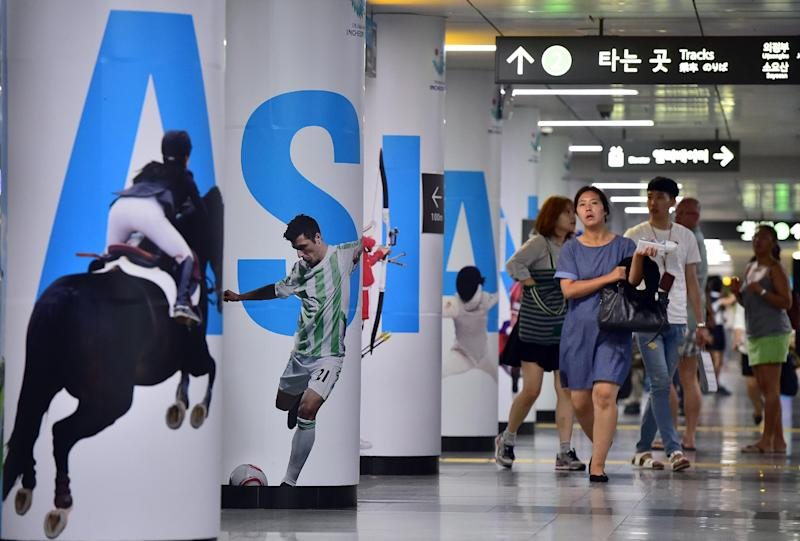 A woman walks past posters of the 2014 Incheon Asian Games at a subway station in Seoul on July 18, 2014