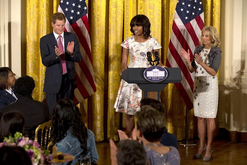 First lady Michelle Obama, center, with Jill Biden, introduces a surprise visit from Prince Harry at an event in honor of military mothers in the East Room of the White House in Washington, Thursday, May 9, 2013. (AP Photo/Jacquelyn Martin)