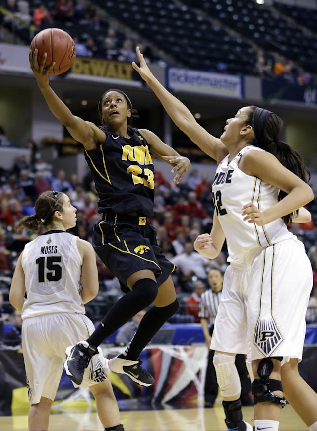 Iowa guard Theairra Taylor, left, shoots over Purdue forward Whitney Bays during the second half of an NCAA college basketball game in the quarterfinals of the Big Ten women's tournament in Indianapolis on Friday, March 7, 2014. Iowa defeated Purdue 87-80. (AP Photo/Michael Conroy)