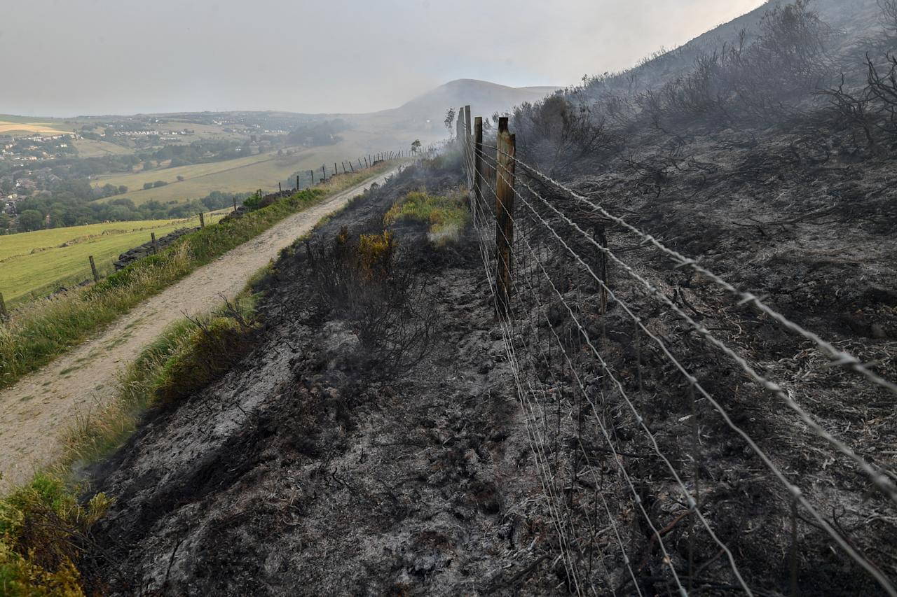 <p>Scorched heather can be seen where a large wildfire has burnt the the moors above Stalybridge, Greater Manchester on June 27, 2018 in Stalybridge, England. Firefighters have declared a 'major incident' as they battle the huge moorland fire which measures 6km. (Photo from Anthony Devlin/Getty Images) </p>