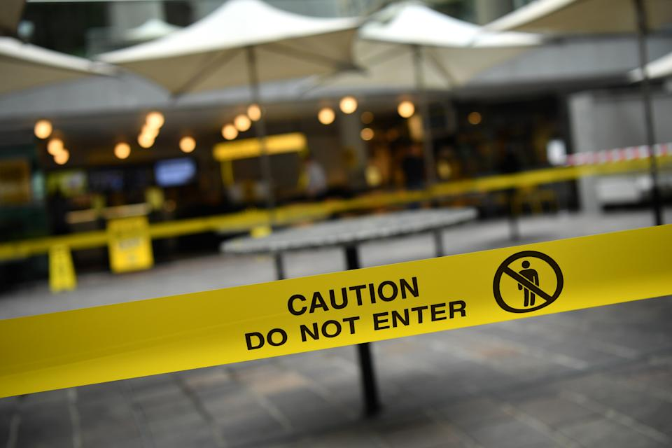 'Caution do not enter' reads yellow tape stretched across an outdoor seating area.